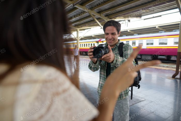 Man photographer taking picture of woman in train station
