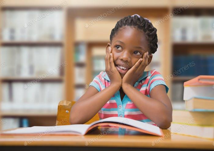 Niña escolar en la biblioteca de la educación