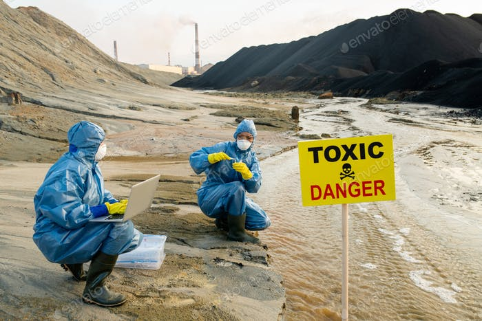 Two ecologists in protective coveralls studying characteristics of toxic water