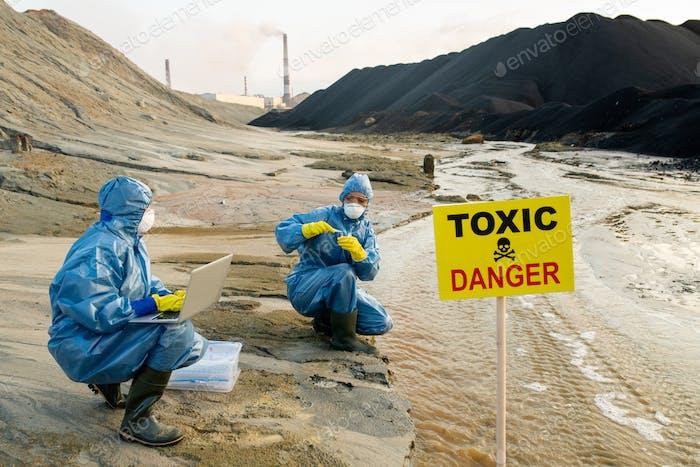 Zwei Ökologen in Schutzanzüge, die Eigenschaften des toxischen Wassers untersuchen