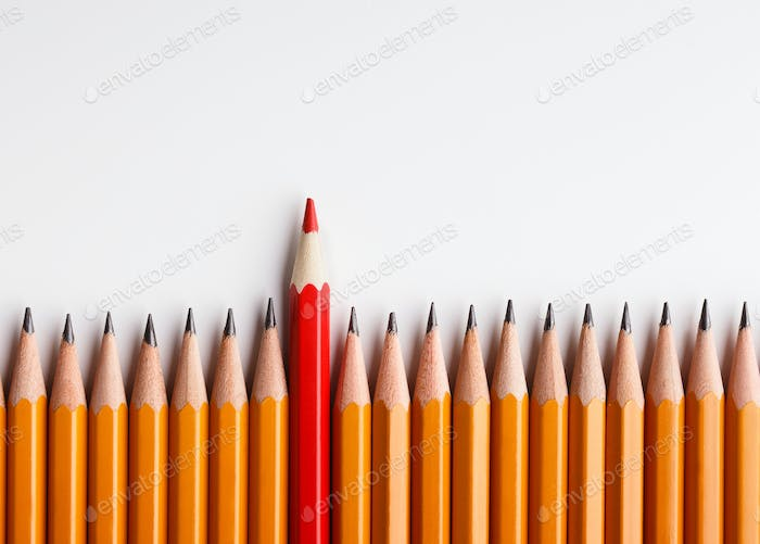 One red pencil standing out of line with similar ones