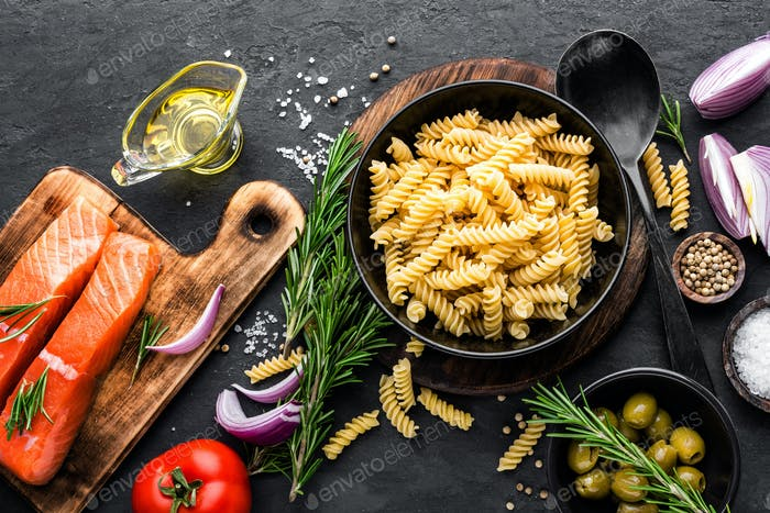 Pasta, salmon fish and ingredients for cooking on black background, top view. Italian food