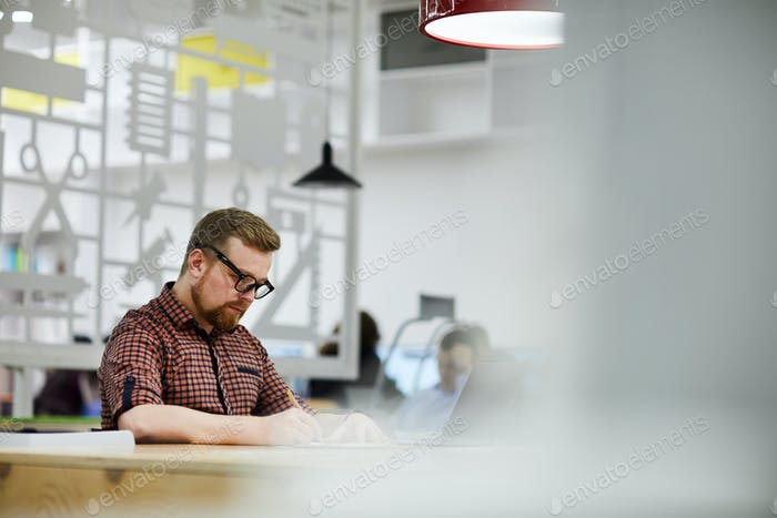 Busy student guy working on scientific papers