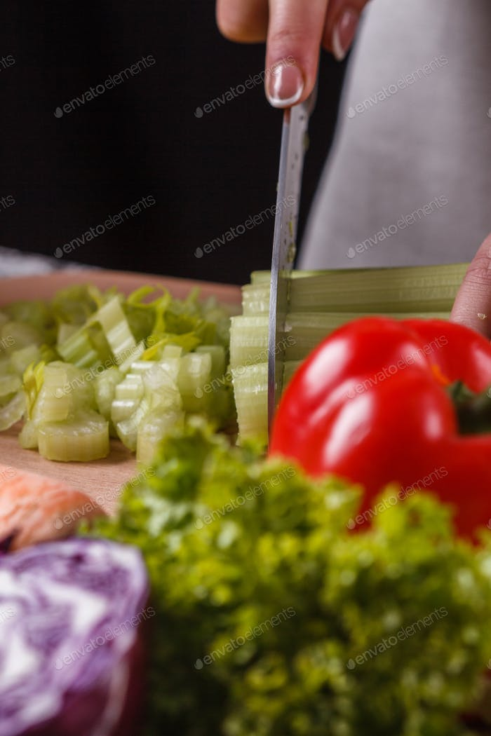 young woman in a gray apron cuts a celery