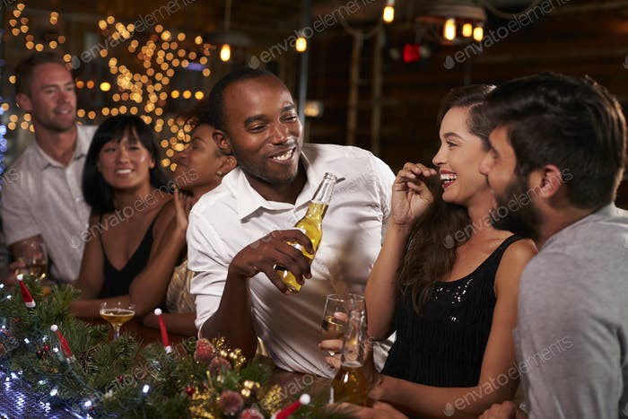 Friends enjoying a Christmas party talk at the bar
