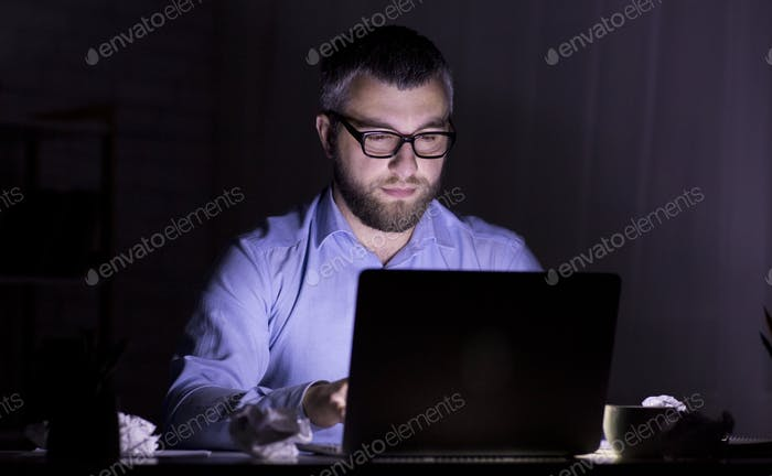 Puzzled man looking at laptop screen in dark room