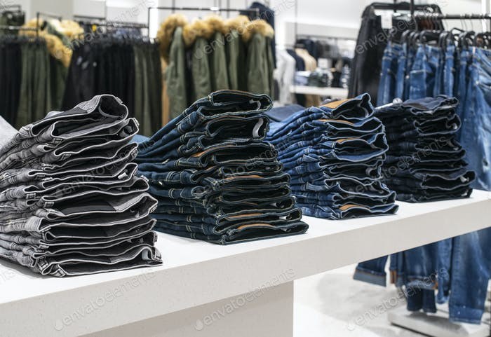 Blouses and jeans on shelf in fashion clothing store. Casual clo