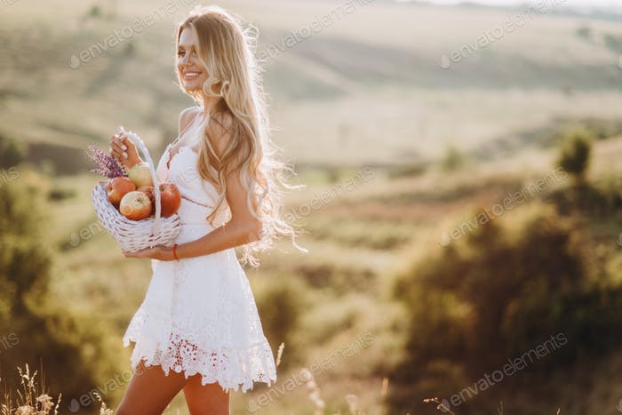 Beautiful sexy blonde girl in white dress posing in a field at sunset with a basket of fruit