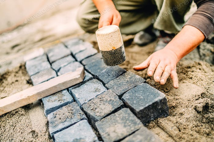 Male construction worker using granite cobblestone blocks to create path or sidewalk