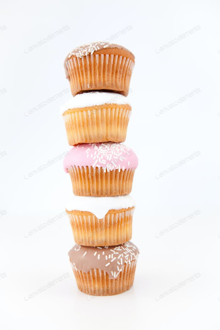 Five muffins with icing sugar piled up against a white background