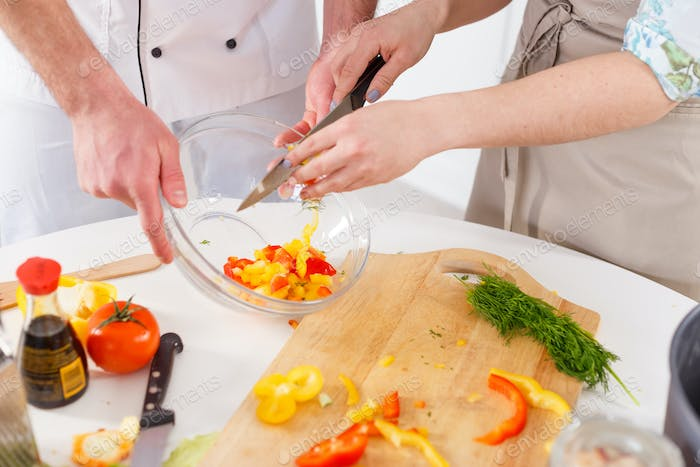A woman is preparing a salad led by a professional chef.