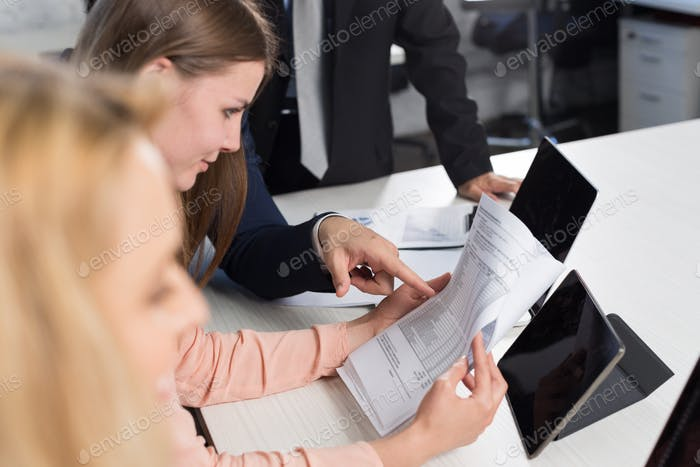 Group Of Business People Discussing Documents On Meeting In Creative Office At Desk, Businesspeople