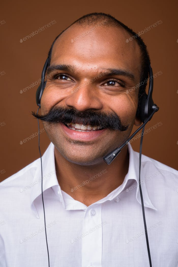 Face of happy Indian businessman with mustache as call center representative