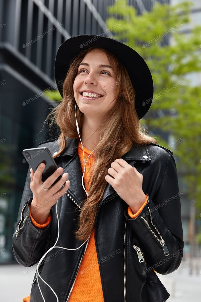 Optimistic lovable woman listens radio online, enjoys song in electronic earphones, has dreamy cheer