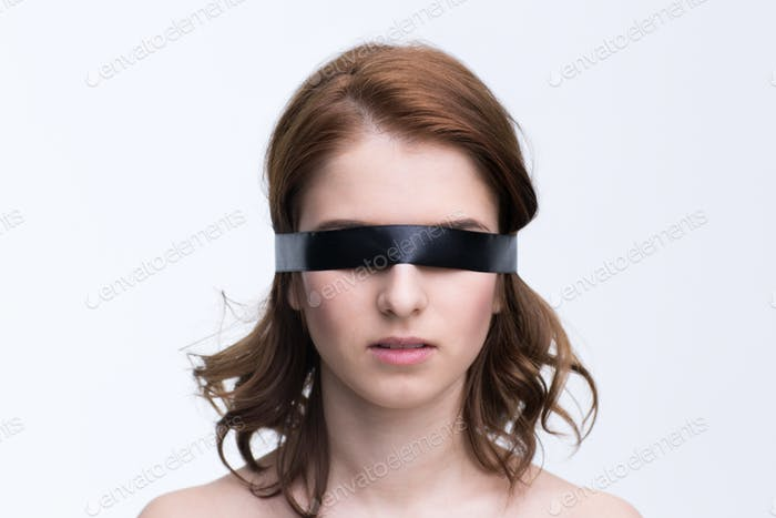 Blindfold young woman over gray background