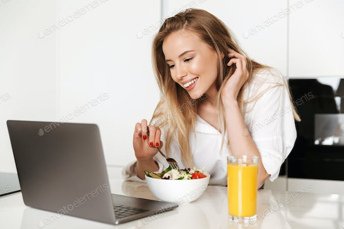 Happy young woman eating salad from a bowl