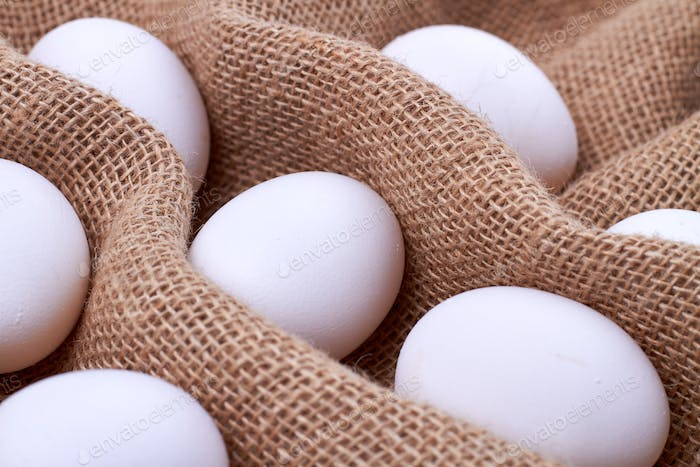 White chicken's eggs on a jute cloth.