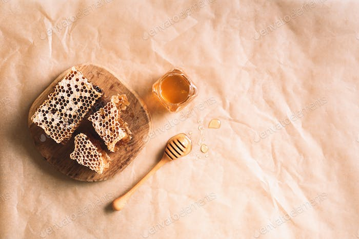 Honeycomb and honey jar with dipper on craft paper backdrop. Copy space. Top view.