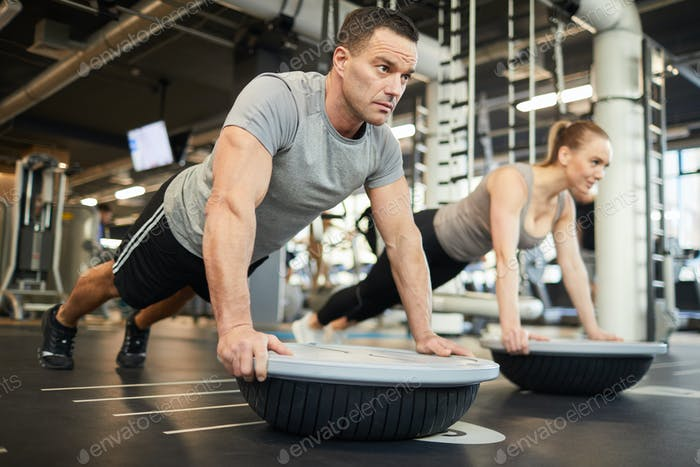 Sportive Couple Doing Balance Exercises in Gym
