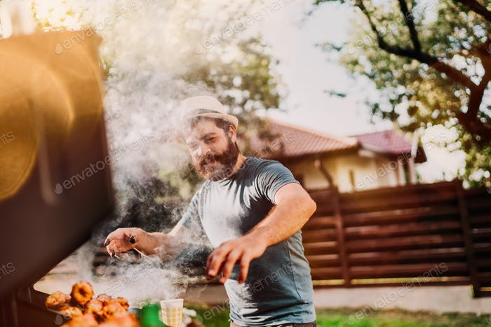 Portrait of man hand cooking barbeque and grilled meat barbecue party at backyard.