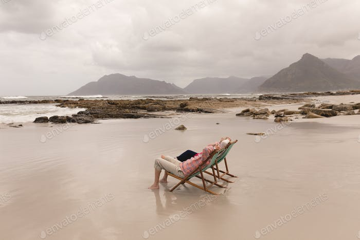 Side view of active senior couple relaxing with hands behind head in a sun lounger on the beach
