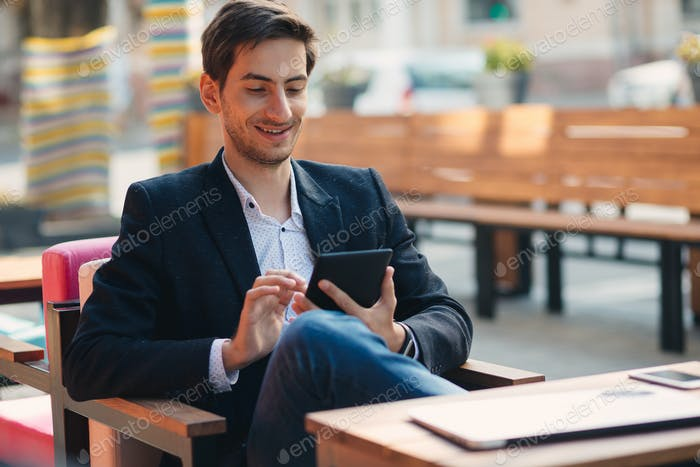 Young man reading digital book smiling while enjoying content