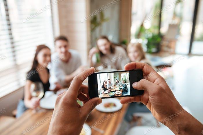 Nahaufnahme des Menschen, der Bilder von Freunden mit Handy