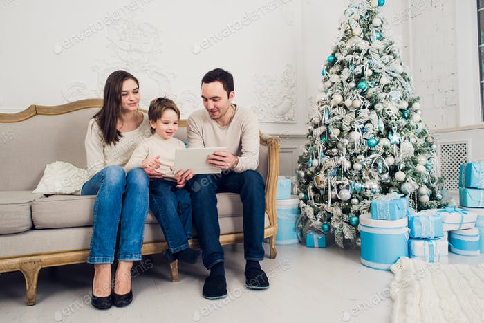 Cheerful family sitting in the living room having fun with the digital tablet that Santa Claus