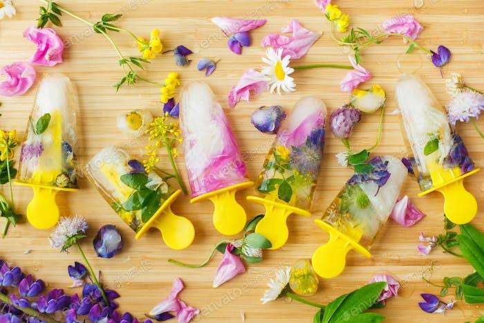 Flores silvestres coloridas en paletas congeladas y cubitos de hielo