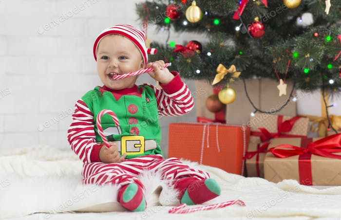 Happy enjoying sweet candy under Christmas tree