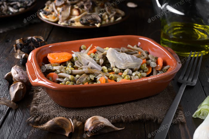 vegetable stew in clay dish, on dark wood table