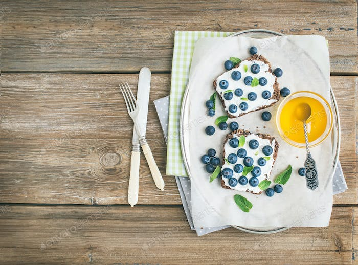 Healthy breakfast set with ricotta, fresh blueberries, honey and