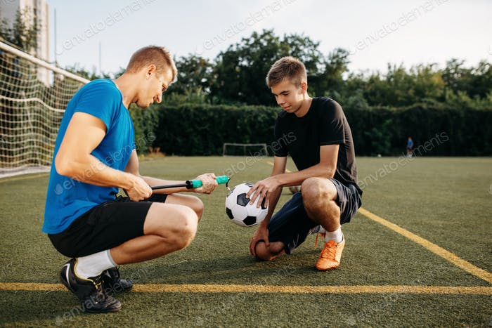Male soccer players pump up the ball on the field
