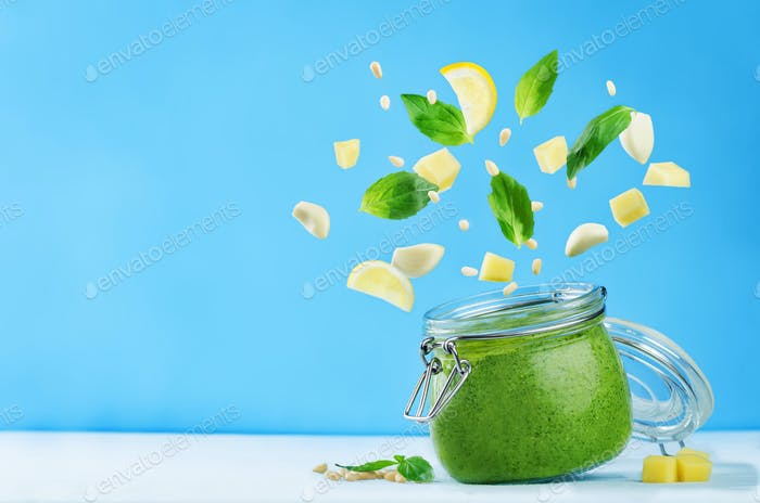 Pesto sauce with flying ingredients to prepare it