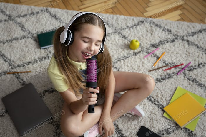 Girl listening to music and singing in brush