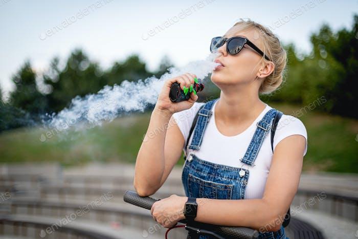 Modern woman outdoor smoking e-cigarette at city street