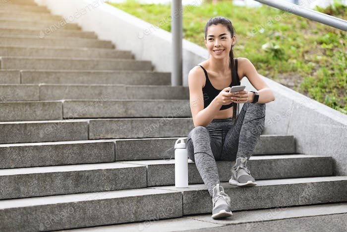 Pretty young asian woman resting after jogging outdoor, sitting on urban stairs