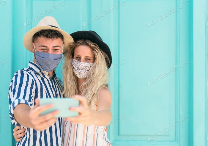 Young couple wearing face mask taking selfie with mobile smartphone on vacation