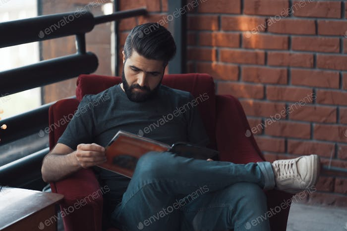 Portrait handsome bearded man wearing casual clothing, sitting in red chair modern loft studio