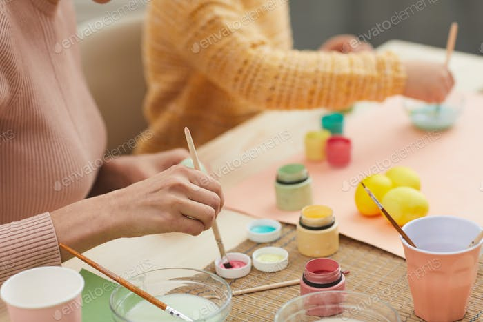 Young Woman Hand Painting Easter Eggs with Daughter