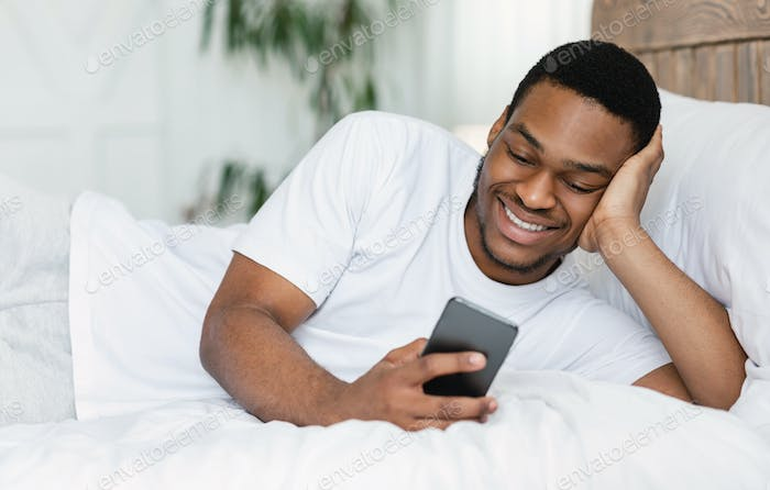 African Guy Using Cellphone Browsing Internet Lying In Bed Indoor