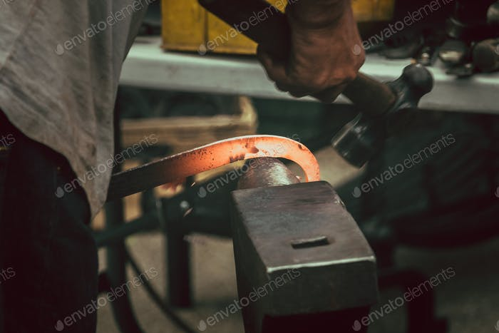 A blacksmith hammering hot iron