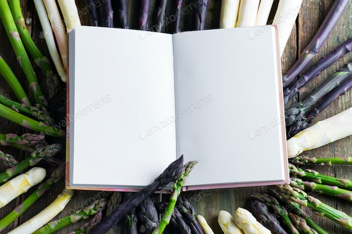 Note book for recipe of healthy dishes on a background from fresh ripe organic asparagus vegetables