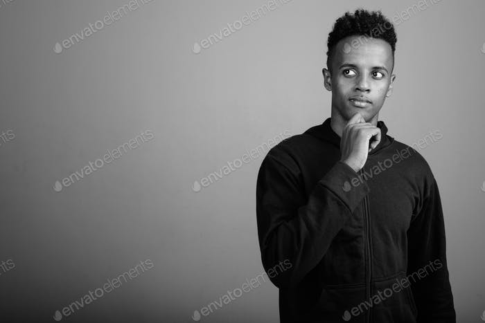 Young handsome African man wearing hoodie against gray background