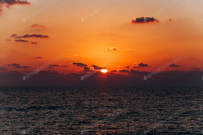 Beautiful sunset over the sea. Reflection of sunset in the sea. Orange sunset.
