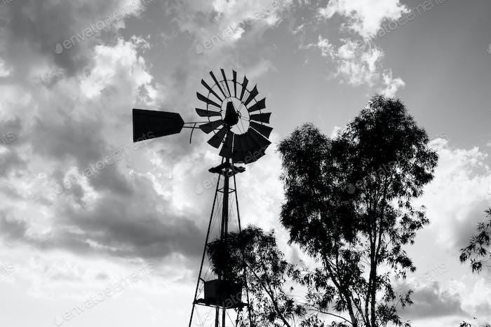 Silhouette einer arbeitenden Vintage-Land-Windmühle in Sonnenuntergangslicht oder Dämmerung.