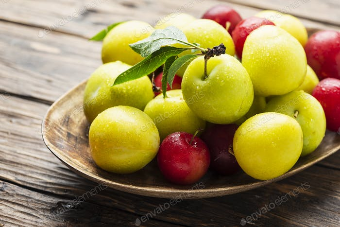 Fresh sweet plums on the wooden table