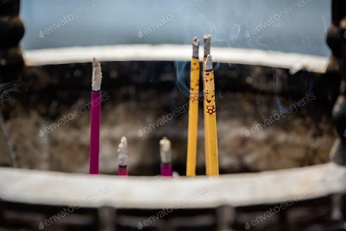Incense sticks burning inside brass pot in a temple