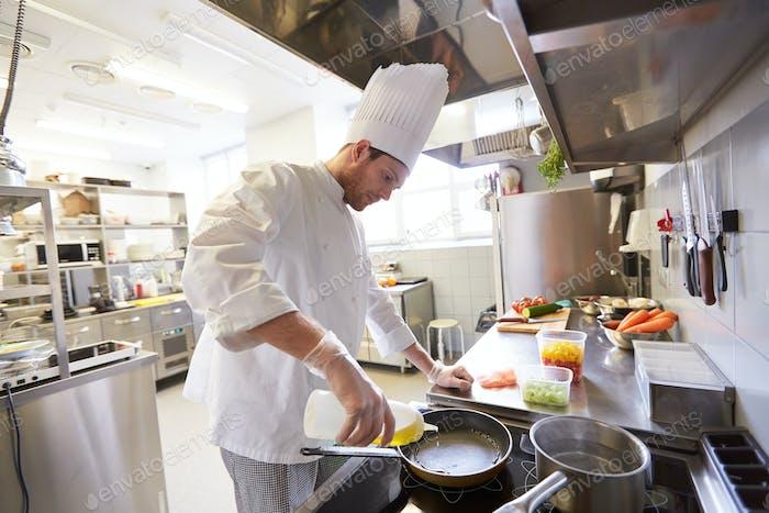 Alegre chef masculino cocinar la Comida en la Cocina del Restaurante