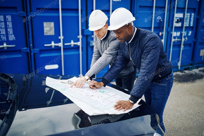 Two engineers standing in a shipping yard discussing blueprints together